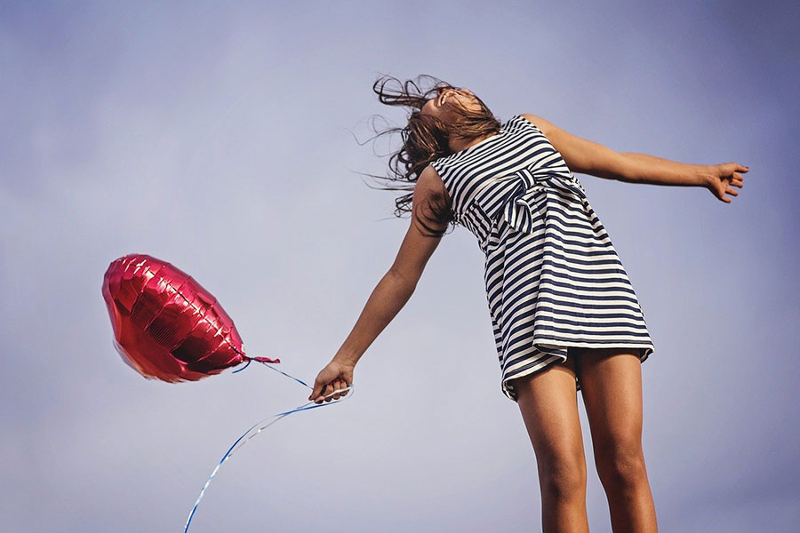 happy woman with heart shaped balloon